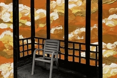 A photograph of a white plastic lawn chair sitting on a platform among painted orange clouds.