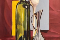 Still life of a wine bottle, tall stemmed white glass, and steel pitcher among a red fabric backdrop.