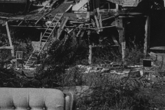 black and white photo of a strange broken down haunted looking house.