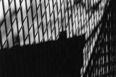 black and white image of a chain link fence from the side.
