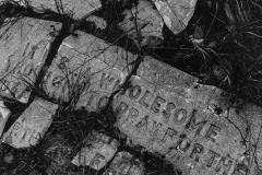 black and white image of words written on brick.