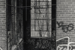 black and white image of an abandoned, graffitied building through a doorway.