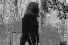 black and white image of a woman dressed in black in a graveyard.