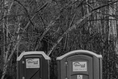 black and white image of two port-o-potties.