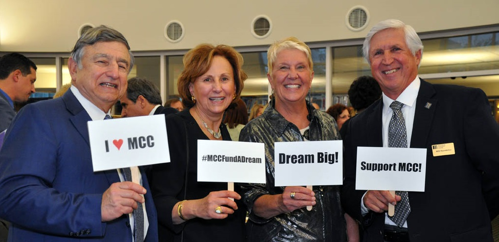 MCC Foundation members holding signs