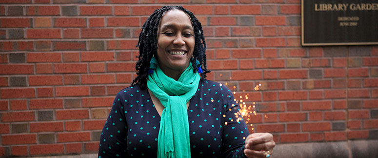 Interim CEO Tanya Millner-Hardee smiling and holding a sparkler