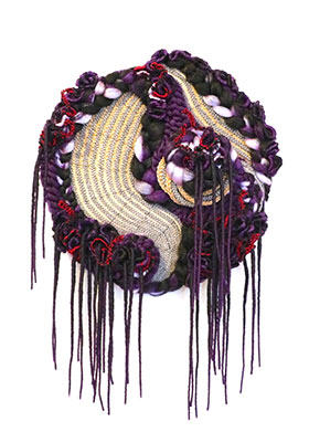 Piece of art with many different materials and threads of different colors, shaped like a circle with threads hanging off the bottom