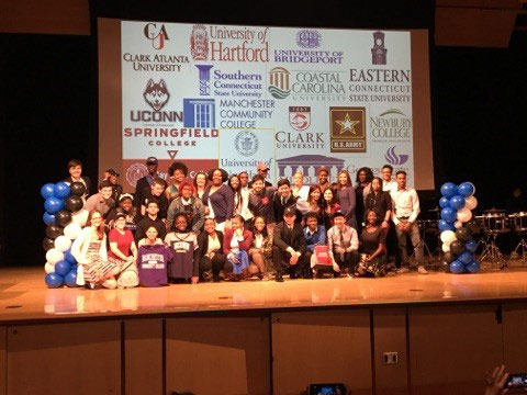 A group of Great Path Academy students gathered on a stage with an array of college logos behind them