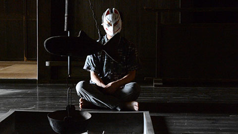 A man sitting cross-legged wearing a white Japanese-style fox mask