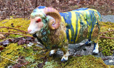 Porcelain lamb figure with various paint colors dripped over its back standing on a moss-covered rock