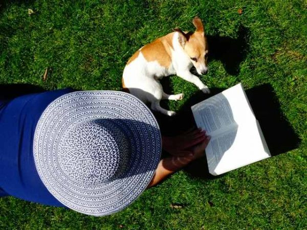 Women in a blue sun hat relaxing with a good book and her dog